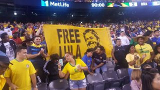 No jogo Brasil e EUA, comitê pede Lula Livre; em vídeo, denuncia lavagem cerebral da Globo; veja